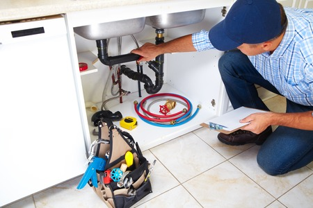 45779475 - plumber with plumbing tools on the kitchen. renovation.