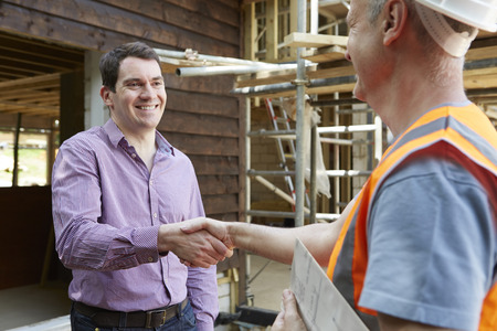42647602 - customer shaking hands with builder